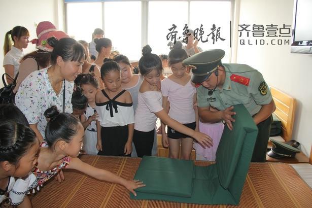 """亲子团参观了官兵宿舍,整齐划一的物品摆放、干净有序的内务设置,尤其是""""豆腐块""""状的被子,给他们留下了深刻的印象。"""