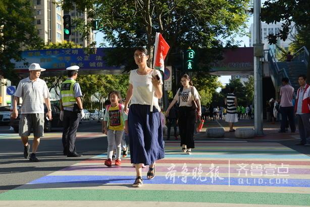"""配合彩虹斑马线,日照交警直属大队又制作了大量""""车让人、人快走""""的礼让手旗,几个学生们一集中,排头的举起小旗,一起过斑马线。为了让小旗有个家,我们又在路口四角的信号灯杆上专门铸造了""""礼让手旗驿站"""",配上了倡导语""""车让人、人快行,小习惯、大文明""""、青年女画家孙丽手绘的漫画图示,进行更具体的指导。学生们在到达对面后,再将小旗插入驿站内,完成传递与接力。"""
