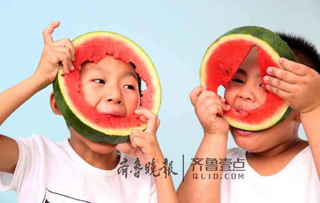 """李昕诺(右一)和小伙伴们在一起吃西瓜""""啃秋""""。 齐鲁晚报·齐鲁壹点 通讯员 吉喆  耿德刚 摄"""
