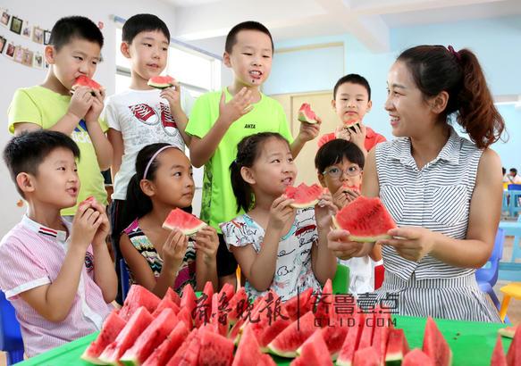 """石碑社区演讲与口才训练基地的老师曹菲(右一)在给小朋友们讲民间""""啃秋""""的习俗。"""