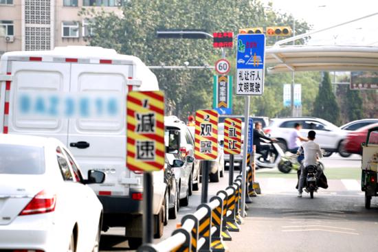 """经十路与舜耕路路口的右转车道旁新增了一组""""减速、观察、礼让""""的警示牌,提醒右转车辆礼让行人、文明驾驶。"""