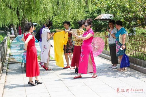 一群阿姨穿上清凉的裙装来到中山公园赏荷。