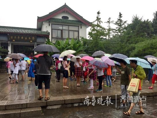 29日上午虽然下雨,气温很凉,但大明湖畔仍有不少游人打着伞沿着湖边漫步,享受夏日降雨带来的清凉。近来天气一直下雨,游人们出门都是有备而来。  齐鲁晚报齐鲁壹点记者 宋磊